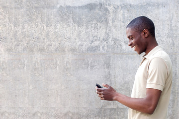 smiling african american man walking and looking at cellphone