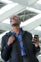 young black businessman walking with cellphone