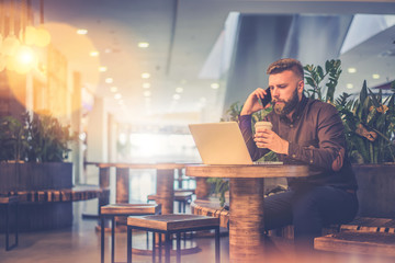 Young bearded businessman, dressed in a brown shirt, sitting at table in coffee shop and reading information from laptop screen while holding cup of coffee and talking on cellphone.Man uses gadget.