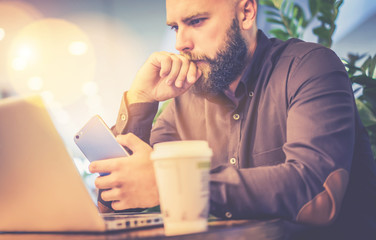 Young bearded businessman, dressed in a brown shirt, sitting at office desk and reading information from laptop screen while holding smartphone. On table is cup of coffee. Man uses gadget.Home plant.