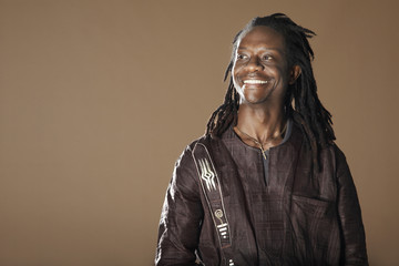 Smiling African American man with dreadlocks looking away on brown background