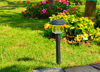 Solar-powered lamp on garden background