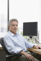 Portrait of a serious mature businessman sitting at office desk