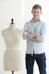 Portrait of young man standing arms crossed by mannequin in fashion studio