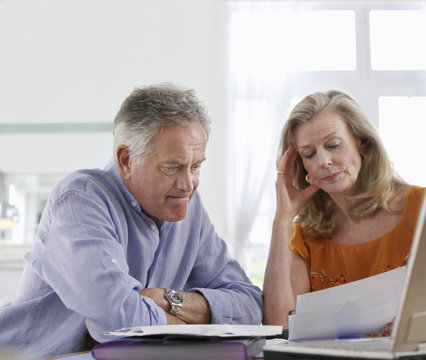 Worried mature couple with bills sitting at dining table in house