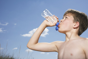 Side view of a shirtless boy drinking from water bottle against sky