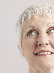 Closeup of smiling senior woman looking away isolated on grey background