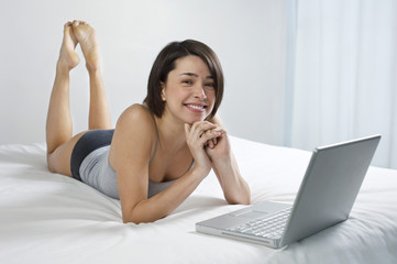 Portrait of a beautiful and relaxed young woman with laptop in bed