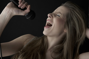 Closeup of passionate teenage girl singing into microphone on black background