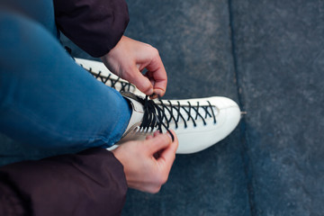 Girl tying laces on the skates