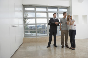 Full length of a male real estate agent showing couple new apartment as woman photographs