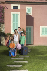 Full length portrait of a couple with three children and luggage in front of house