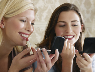 Closeup of two beautiful young women putting on makeup