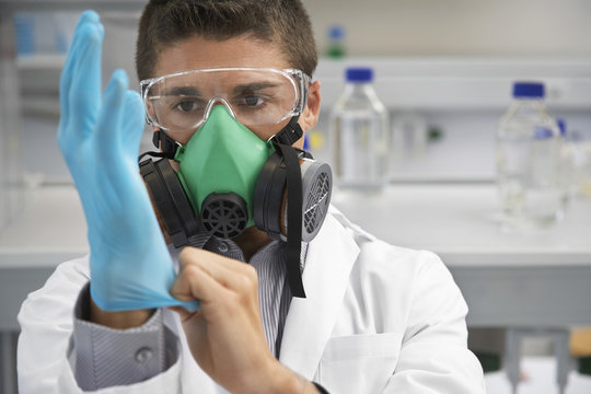 Male scientist in a gas mask while putting on rubber glove in laboratory