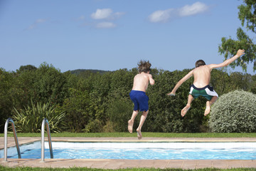 Full length rear view of two shirtless boys jumping into swimming pool