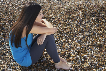 Full length of thoughtful young woman sitting on pebbles at beach