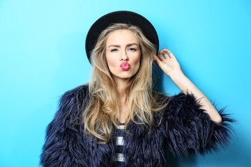 Young cool woman in fur and hat on blue background