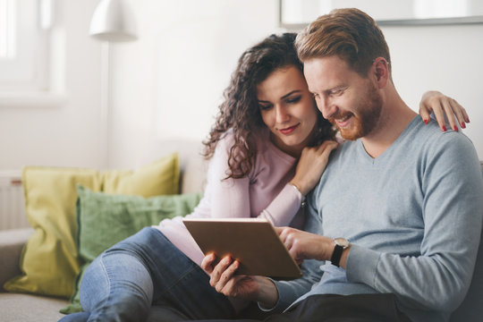 Happy couple surfing on tablet at home