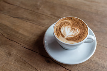 hot cappuccino with latte art in heart shape on a wooden background