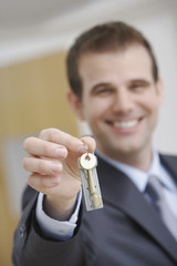 Blurred happy male real estate agent holding out house key
