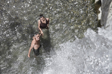 Top view of a happy couple holding hands under waterfall