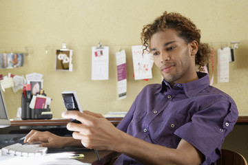 Young African American man using cellphone by computer in the office