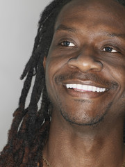 Closeup of African American man smiling on gray background
