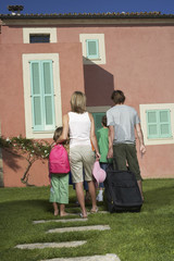 Full length rear view of a couple with three children and luggage in front of house