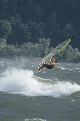 Side view of a man jumping whilst windsurfing