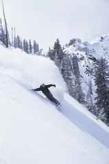 Distance shot of a silhouette snowboarder on slope