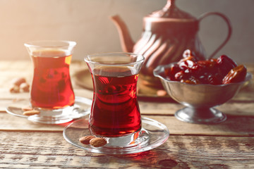 Turkish tea in traditional glasses on wooden table closeup