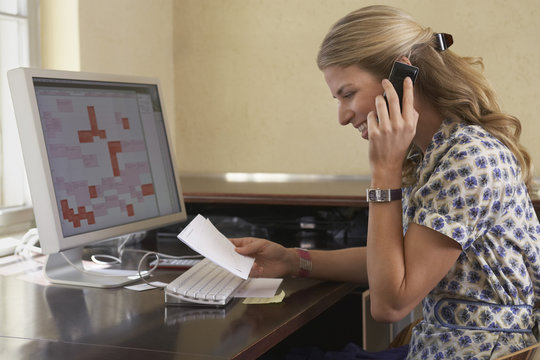 Side view of a smiling young woman reading papers and using cellphone in office