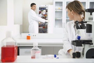 Scientist using microscope with male colleague looking in refrigerator in laboratory