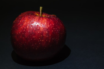 red apple with drops of dew on a black background