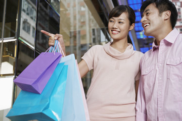 Happy young man with woman carrying shopping bags while pointing at window display