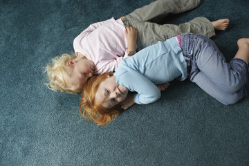 High angle portrait of little girl lying with sister sleeping on carpet at home