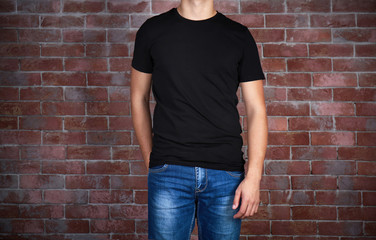 Handsome young man in blank black t-shirt standing against brick wall, close up