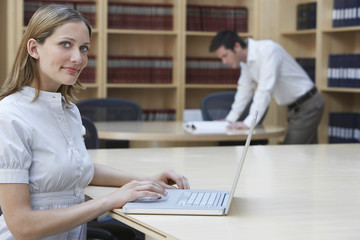Side view of a female office worker using laptop in legal office
