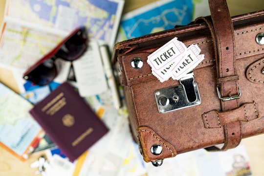 Tickets and Suitcase with Passport and Sunglasses