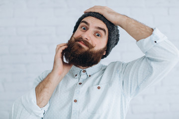Stylish bearded and mustache man in a cap and shirt scratching his beard.
