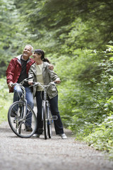 Cheerful mature man and middle aged woman with bikes on forest road