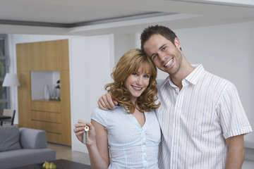 Portrait of a happy young couple with key in new home