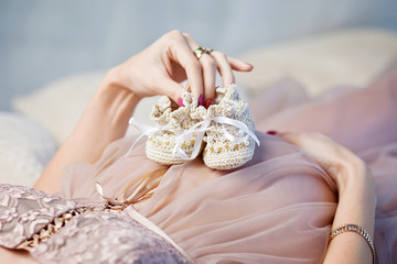 Newborn baby booties in mothers hands. Pregnant woman belly.Clos
