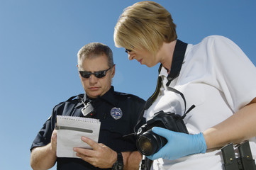 Low angle view of police officer and investigator with camera