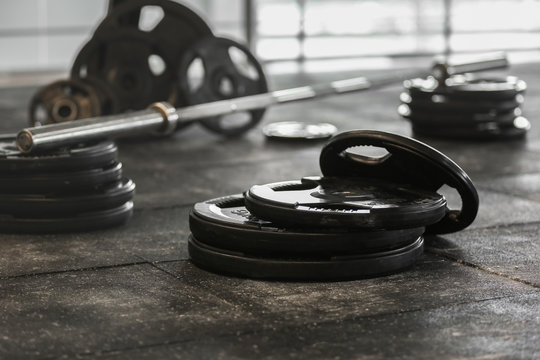Disassembled barbell on floor in gym