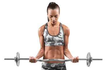 Sporty young woman with barbell  on gray background