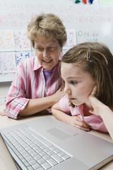 Teacher helping schoolgirl use laptop in classroom