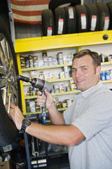 Portrait of a mechanic holding electronic screw fitter at workshop