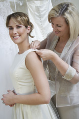 Mother helping bride to put her wedding dress on