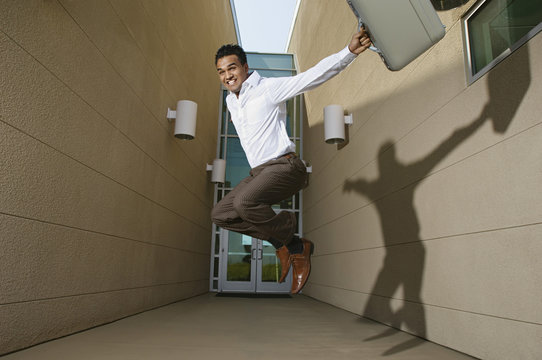 Happy young successful businessman jumping against entrance of office building